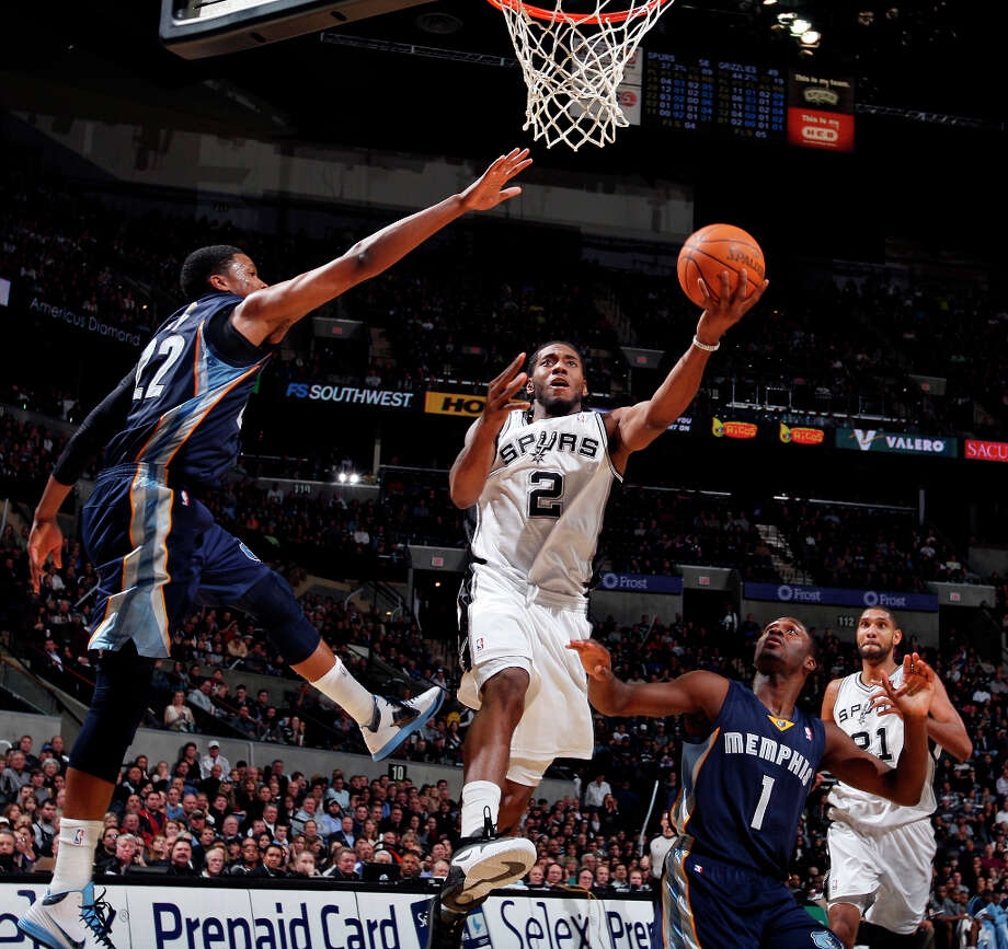 Spurs' Kawhi Leonard shoots between  Grizzlies' Rudy Gay (left) and Jeremy Pargo as Spurs' Tim Duncan looks on Dec. 26, 2011 at the AT&T Center. The Spurs won 95-82. Photo: EDWARD A. ORNELAS, SAN ANTONIO EXPRESS-NEWS / SAN ANTONIO EXPRESS-NEWS (NFS)