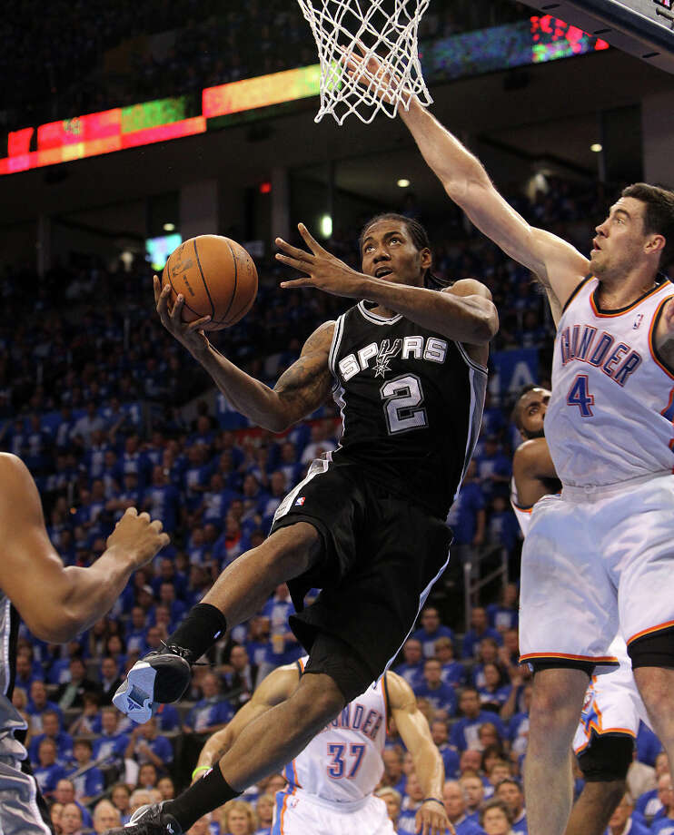 Spurs' Kawhi Leonard (2) drives to the basket against  Thunder's Nick Collison (4) during the first half of Game 3 of the NBA Western Conference Finals in Oklahoma City, Okla. on Thursday, May 31, 2012. Photo: Kin Man Hui, San Antonio Express-News / © 2012 San Antonio Express-News