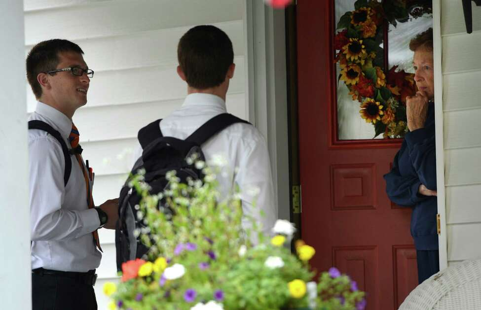 Mormon missionaries, Elder Caden Portela of Firth, Idaho, left and Elder Kenny Seymour of Anaheim, California speak to Rosemary Bradley on Harris Street during their missionary work in Albany, N.Y. Oct. 4, 2012. (Skip Dickstein/Times Union)