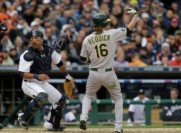 Oakland Athletics' Josh Reddick (16) signals for teammate Yoenis Cespedes to run from third as Detroit Tigers catcher Gerald Laird chases a wild pitch during the eighth inning of Game 2 of the American League division baseball series, Sunday, Oct. 7, 2012, in Detroit. (AP Photo/Paul Sancya) Photo: Paul Sancya
