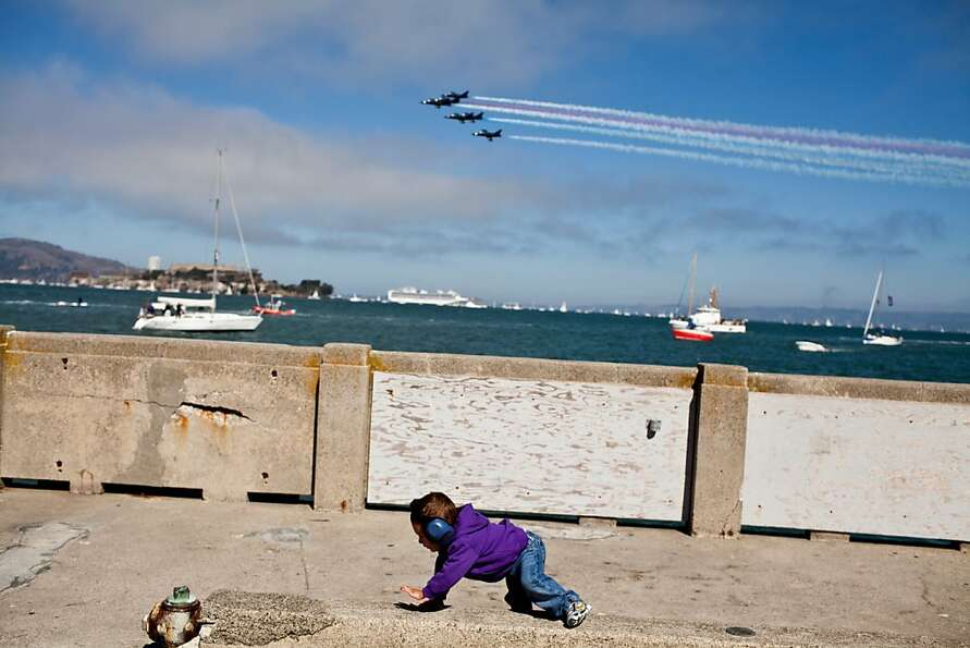 Wyatt Laferriere, 2, crawls on the group as the Patriots Jet Team fly overhear during the Fleet Week