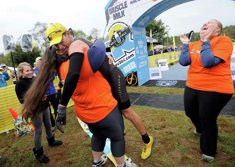 Cancer survivor Jessica Protasio, of Columbia, Md., gives Lance Armstrong a hug and a lift on Sunday after he competed in the Rev3 Half Full Triathalon. Photo: Steve Ruark / FR96543 AP