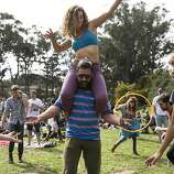 Amy Winzer dances on the shoulders of Brad Graevs with Lauren Saint (left) and Jes Hagan (right) while listening to the performance of the band Soul Rebels at the Towers of Gold Stage during the last day of Hardly Strictly Bluegrass in Golden Gate Park in San Francisco, Calf., on Sunday, October 7, 2012.