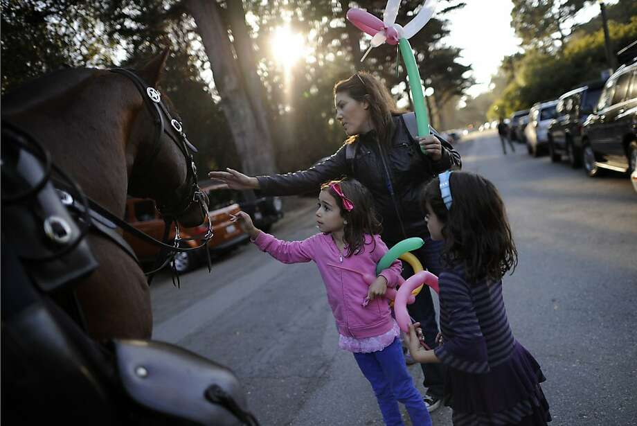 "On their way out of the festival, Palmer Dean, in pink, and her sister Harper Dean with Ceci Aviles-Fisher pet police horse ""Zippo"" ridden by Sgt. Totan.  Day 3 of the Hardly Strictly Bluegrass festival in Golden Gate Park in San Francisco, CA Sunday October 7th, 2012. Photo: Michael Short, Special To The Chronicle"
