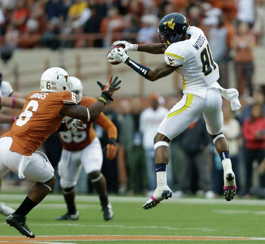West Virginia's J.D. Woods finds a hole in the Texas secondary during the second quarter Saturday night. Photo: Eric Gay / AP