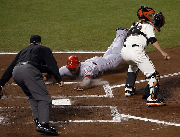 Joey Votto slides past Buster Posey waiting for the throw on a Scott Rolen single in the fourth inning. The San Francisco Giants played the Cincinnati Reds at AT&T Park in San Francisco, Calif.,  in Game 1 of the National League Division Series on Sunday, October 7, 2012. Photo: Carlos Avila Gonzalez, The Chronicle