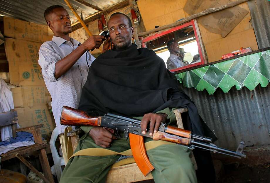 Do you want bangs?A fighter of the pro-government Ras Kimboni  Brigade gets a trim inside a barber's kiosk in the southern Somali port  city of Kismayo. Photo: Stuart Price, AFP/Getty Images