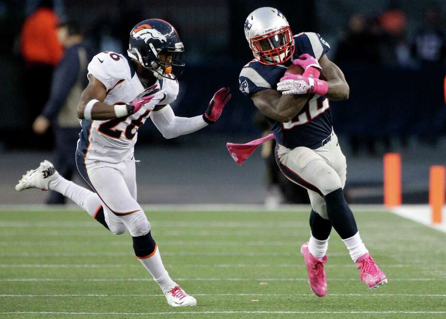 The Patriots' Stevan Ridley, right, trying to get away from Broncos safety Rahim Moore, managed to stand out in a game matching two high-profile quarterbacks by rushing for 151 yards. Photo: Stephan Savoia / AP