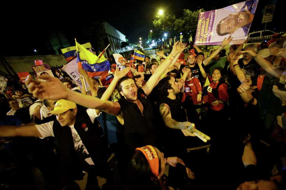 Supporters of Venezuela's President Hugo Chavez cheer after polling stations closed and before any results were made available outside Miraflores presidential place in Caracas, Venezuela, Sunday, Oct. 7, 2012. Chavez is running for re-election against opposition candidate Henrique Capriles. (AP Photo/ Fernando Llano) Photo: Fernando Llano