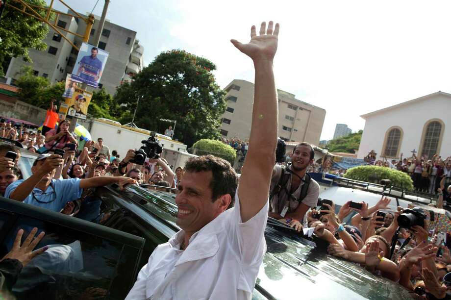 Opposition presidential candidate Henrique Capriles waves to supporters as he leaves a polling station after voting in the presidential election in Caracas, Venezuela, Sunday, Oct. 7, 2012. Capriles is running against President Hugo Chavez. (AP Photo/Ramon Espinosa) Photo: Ramon Espinosa