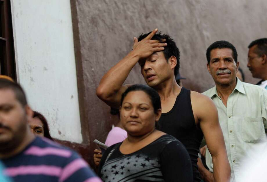 A man wipes his forehead as he waits in line with other voters at a polling station during the presidential election in Caracas, Venezuela, Sunday, Oct. 7, 2012. President Hugo Chavez is running against opposition candidate Henrique Capriles. (AP Photo/Ariana Cubillos) Photo: Ariana Cubillos