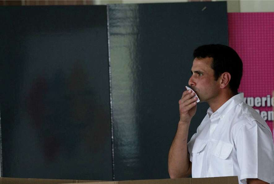 Opposition presidential candidate Henrique Capriles kisses his ballot before putting it in a box as