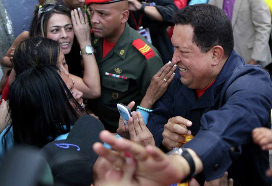 Venezuela's President Hugo Chavez greets people as he arrives to a polling station during the presidential election in Caracas, Venezuela, Sunday, Oct. 7, 2012.  Chavez is running for re-election against opposition candidate Henrique Capriles.  (AP Photo/Rodrigo Abd) Photo: Rodrigo Abd