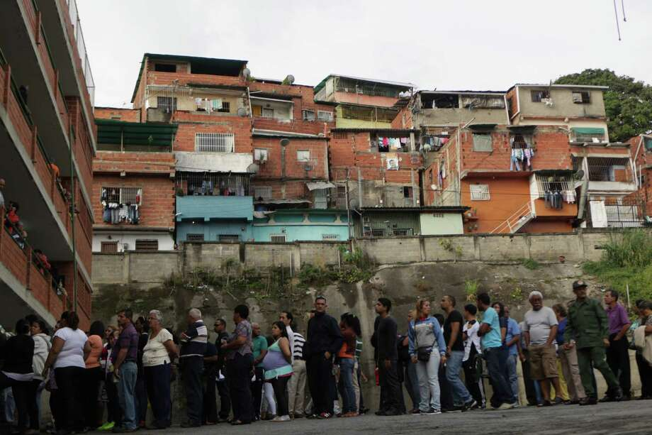 Residents wait in line at a polling station to vote in the presidential election in the Catia neighborhood of Caracas, Venezuela, Sunday, Oct. 7, 2012. President Hugo Chavez is running for re-election against opposition candidate Henrique Capriles. (AP Photo/Rodrigo Abd) Photo: Rodrigo Abd