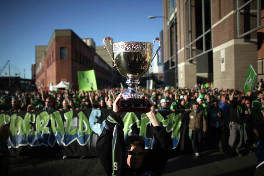 Emerald City Supporters hoist the Cascadia Cup as they march to the match between the Seattle Sounders and Portland Timbers match during a game between the Pacific Northwest rivals on Sunday, October 7, 2012 at CenturyLink Field in Seattle. The Sounders beat the Timbers in front of a Seattle record MLS crowd of more than 66,000 fans. The sounders won 3-0. Photo: JOSHUA TRUJILLO / SEATTLEPI.COM