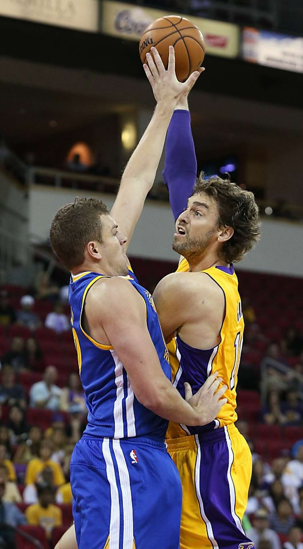 Los Angeles Lakers' Pau Gasol, right, of Spain, puts up a shot against Golden State Warriors defender David Lee in the first half of a preseason NBA basketball game in Fresno, Calif., Sunday, Oct. 7, 2012. (AP Photo/Gary Kazanjian)