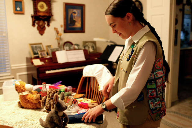 Girl Scout Rebecca Baumgarten, who is visually impaired, touches items that go in the book bags she made for blind and visually impaired children that also include books in braille and print for the Girl Scout Silver Award at her home in Schertz on Thursday, Sept. 27, 2012. Photo: Lisa Krantz, San Antonio Express-News / San Antonio Express-News
