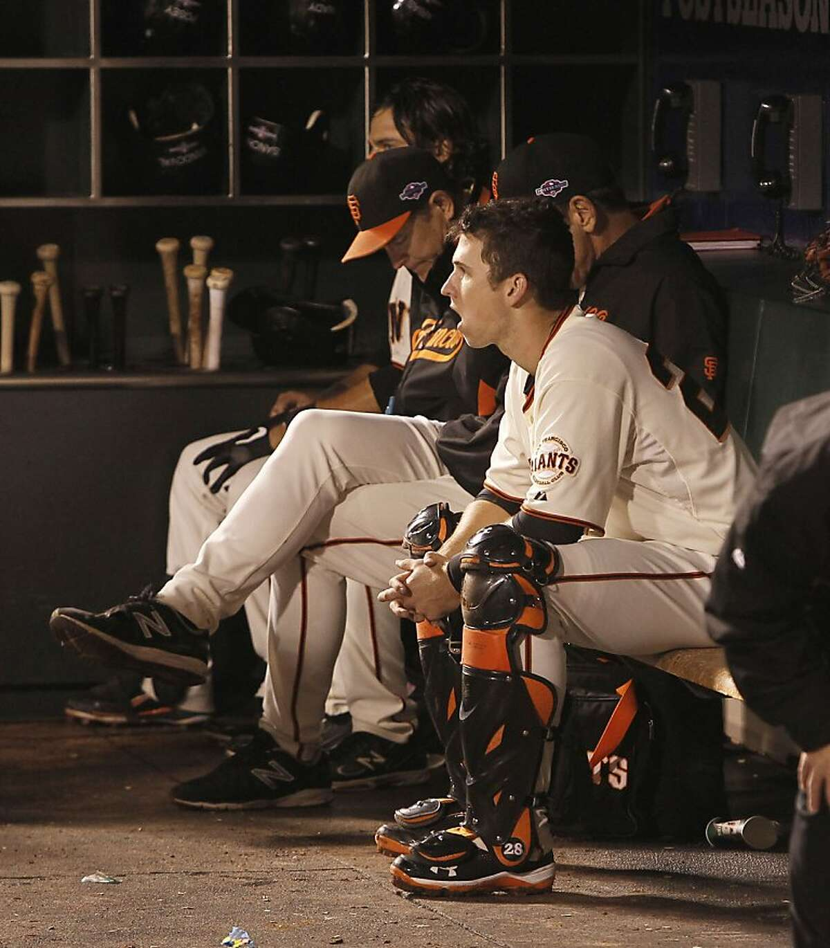 Giants catcher Buster Posey watches from the dugout in the eighth inning as the San Francisco Giants go on to lose to the Cincinnati Reds 9-0 in game two of the National League Divisional Series at AT&T Park San Francisco, Calif., on Sunday October 7, 2012.