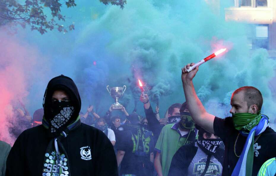 Seattle Sounders supporters march with flares and smoke bombs to the stadium prior to an MLS soccer