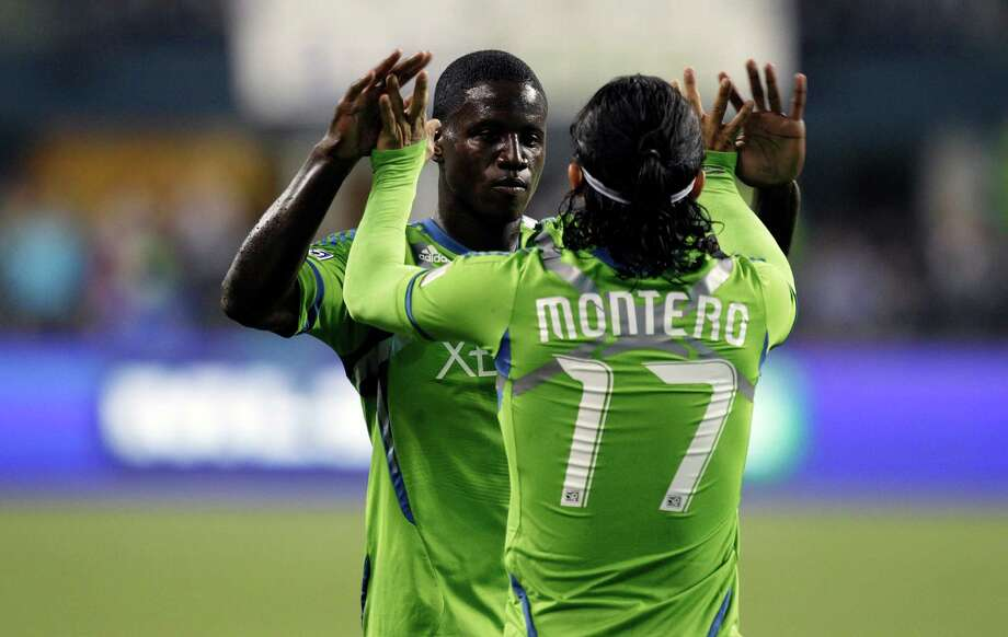 Seattle Sounders' Eddie Johnson, left, greets Sounders' Fredy Montero (17) after Montero scored a goal against the Portland Timbers in the second half of an MLS soccer match, Sunday, Oct. 7, 2012, in Seattle. The Sounders beat the Timbers, 3-0. Photo: Ted S. Warren / Associated Press