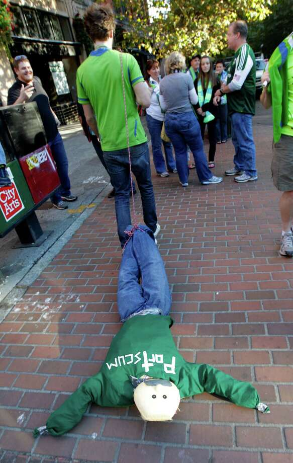 "Philip Jacobsen, of Seattle, drags an effigy of a person wearing a shirt that says ""Portscum,"" a derogatory name for the Oregon city of Portland, as supporters march to the stadium prior to an MLS soccer match between the Seattle Sounders and the Portland Timbers, Sunday, Oct. 7, 2012, in Seattle. Photo: Ted S. Warren / Associated Press"