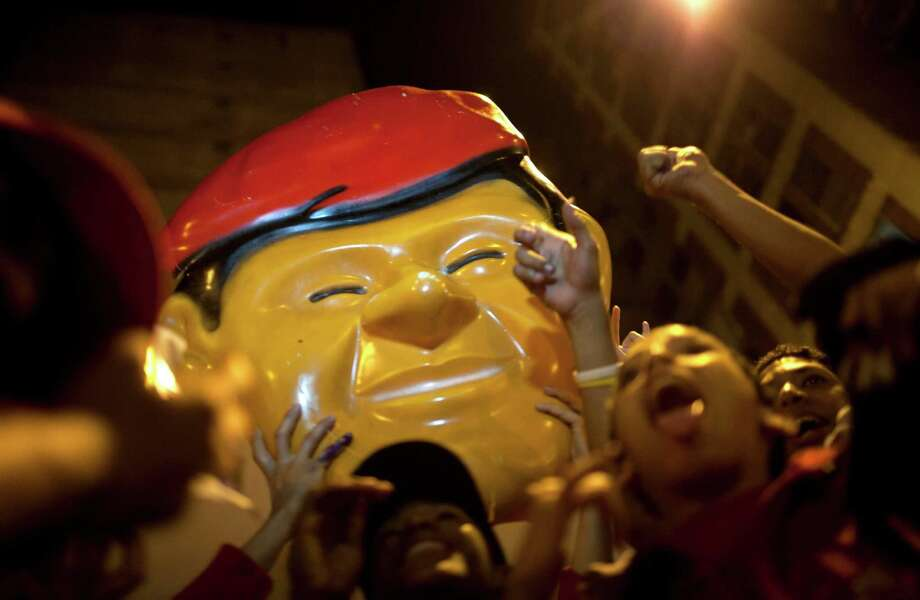 Supporters of Venezuela's President Hugo Chavez celebrate in downtown Caracas, Venezuela, Sunday, Oct. 7, 2012.  Chavez won re-election and a new endorsement of his socialist project Sunday, surviving his closest race yet after a bitter campaign against opposition candidate Henrique Capriles.(AP Photo/Ariana Cubillos) Photo: Ariana Cubillos