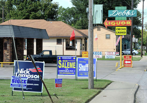 Several political signs are posted Thursday in front of Debb's Liquor on College Street. Store co-owner Frank Messina said that to avoid political conflict at his business, he grants any candidate's request to post a sign on store property. Photo taken Thursday, October 4, 2012 Guiseppe Barranco/The Enterprise Photo: Guiseppe Barranco, STAFF PHOTOGRAPHER / The Beaumont Enterprise