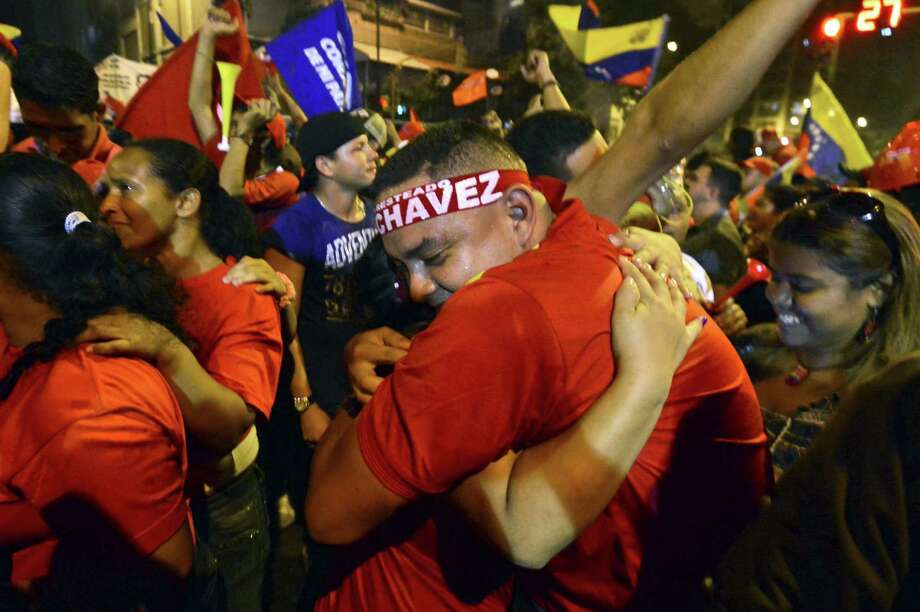 TOPSHOTS  Supporters of Venezuelan President Hugo Chavez celebrate after receiving news of his reelection in Caracas on October 7, 2012. According to the National Electoral Council, Chavez was reelected with 54.42% of the votes, beating opposition candidate Henrique Capriles, who obtained 44.47%. AFP PHOTO/Luis AcostaLUIS ACOSTA/AFP/GettyImages Photo: LUIS ACOSTA, AFP/Getty Images / AFP
