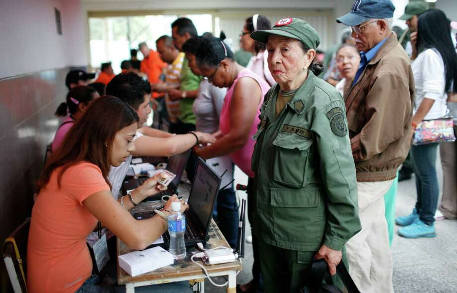 An elderly woman wearing a Bolivarian militia uniform stands before an election worker, who holds her identification as part of the voting process, before casting her ballot in the presidential election at a polling station in the Petare neighborhood of Caracas, Venezuela, Sunday, Oct. 7, 2012.  President Hugo Chavez is running against opposition candidate Henrique Capriles. The Bolivarian militia, created by Chavez, is estimated to number more than 100,000 who do not report to the armed forces. Photo: Ariana Cubillos, AP / AP