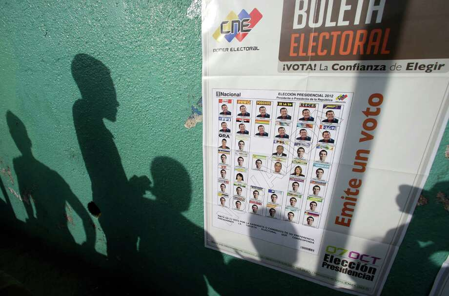 Voters' shadows are cast on a wall as they wait at a polling station during the presidential election in Caracas, Venezuela, Sunday, Oct. 7, 2012. President Hugo Chavez is running against opposition candidate Henrique Capriles. Photo: Fernando Llano, AP / AP