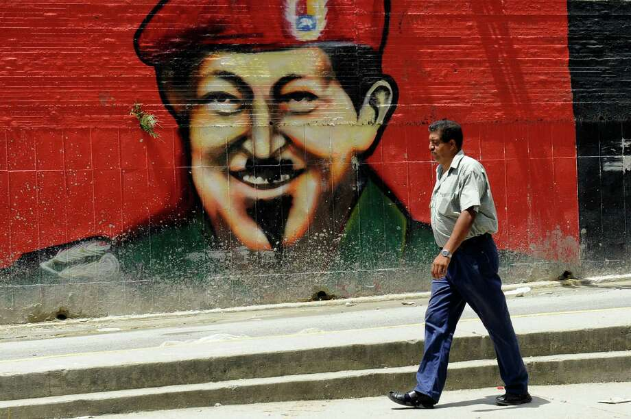 TOPSHOTS A man walks past a mural depicting Venezuelan President and presidential candidate Hugo Chavez in Caracas, on October 6, 2012. Chavez, in power for almost 14 years, is vying for a fourth term in office that would extend his presidency by another six years, but opposition candidate Henrique Capriles hopes to pull a major upset in the presidential elections on October 7. AFP PHOTO/Leo RAMIREZLEO RAMIREZ/AFP/GettyImages Photo: LEO RAMIREZ, AFP/Getty Images / LEO RAMIREZ
