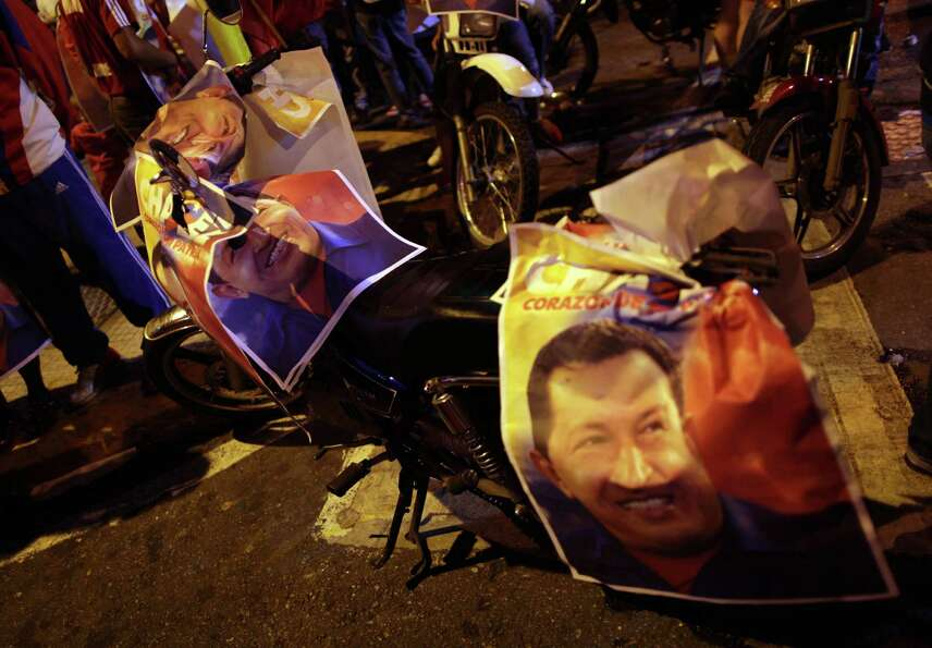A motorcycle covered with posters with images of Venezuela's President Hugo Chavez sits on a street