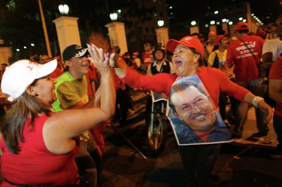 Supporters of Venezuela's President Hugo Chavez cheer after polling stations closed and before any results were made available in Caracas, Venezuela, Sunday, Oct. 7, 2012. Venezuela's electoral council says Chavez has won re-election, defeating challenger Henrique Capriles. Photo: Rodrigo Abd, AP / AP