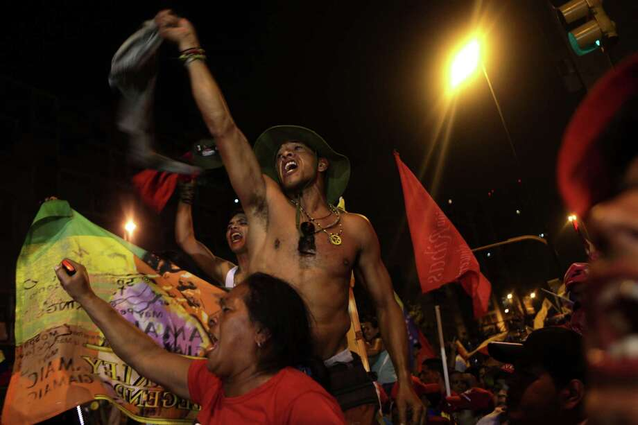 Supporters of Venezuela's President Hugo Chavez celebrate at the Miraflores presidential palace late Sunday Oct. 7, 2012. Chavez won re-election and a new endorsement of his socialist project Sunday, surviving his closest race yet after a bitter campaign against opposition candidate Henrique Capriles. Photo: Rodrigo Abd, AP / AP