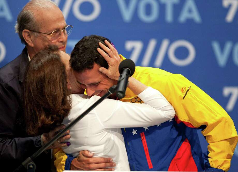 Opposition presidential candidate Henrique Capriles is embraced by his mother Monica Radonski after he conceded defeat in the presidential elections at his campaign headquarters in Caracas, Venezuela, Sunday, Oct. 7, 2012.  Venezuela's electoral council said late Sunday President Hugo Chavez has won re-election, defeating challenger Henrique Capriles. Photo: Ariana Cubillos, AP / AP