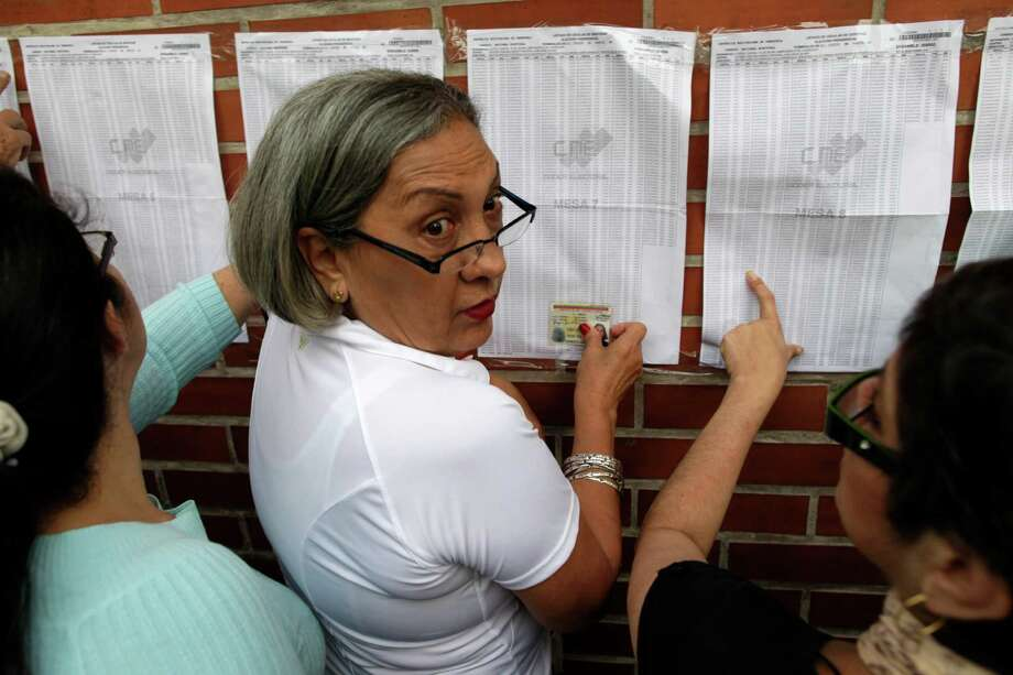 Residents look for their names on voter lists at a polling station during the presidential election in Caracas, Venezuela, Sunday, Oct. 7, 2012.  President Hugo Chavez is running for re-election against opposition candidate Henrique Capriles. Photo: Enric Marti, AP / AP