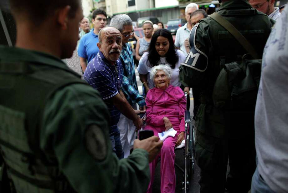 An elderly woman in a wheel chair is helped to enter a polling station during the presidential election in Caracas, Venezuela, Sunday, Oct. 7, 2012. President Hugo Chavez is running against opposition candidate Henrique Capriles. Photo: Ramon Espinosa, AP / AP