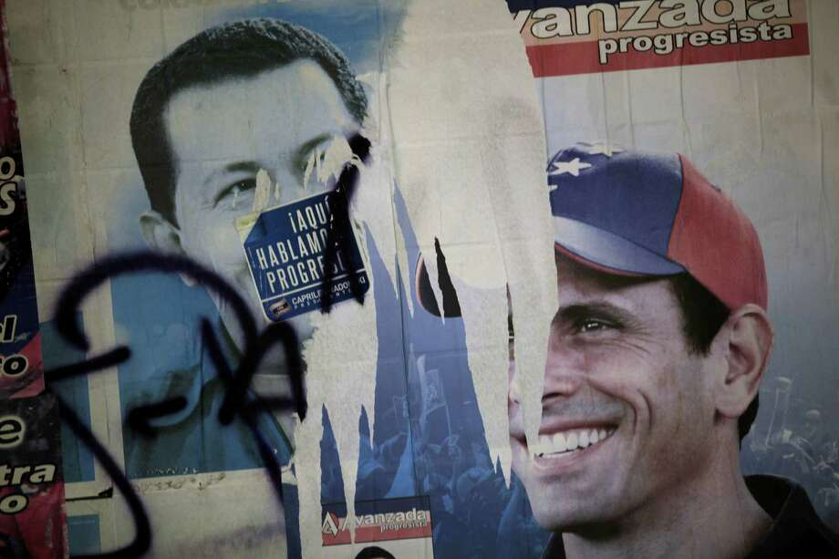 Election campaign posters of presidential candidates, President Hugo Chavez, left, and Henrique Capriles, of the opposition, cover a wall at a polling station during the presidential election in the Catia neighborhood of Caracas, Venezuela, Sunday, Oct. 7, 2012. Photo: Rodrigo Abd, AP / AP