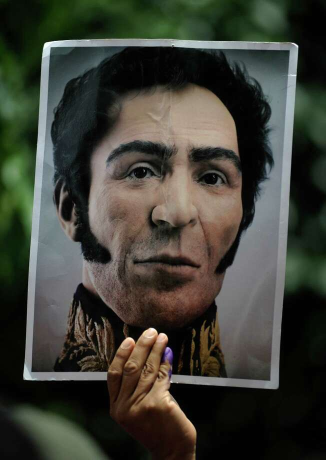 A supporter of Venezuela's President Hugo Chavez, with a pinky finger inked which means the person has already voted in the presidential election, holds a portrait of Venezuela's independence hero Simon Bolivar outside a polling station while Chavez votes in Caracas, Venezuela, Sunday, Oct. 7, 2012. Chavez is running for re-election against opposition candidate Henrique Capriles. Photo: Sharon Steinmann, AP / AP