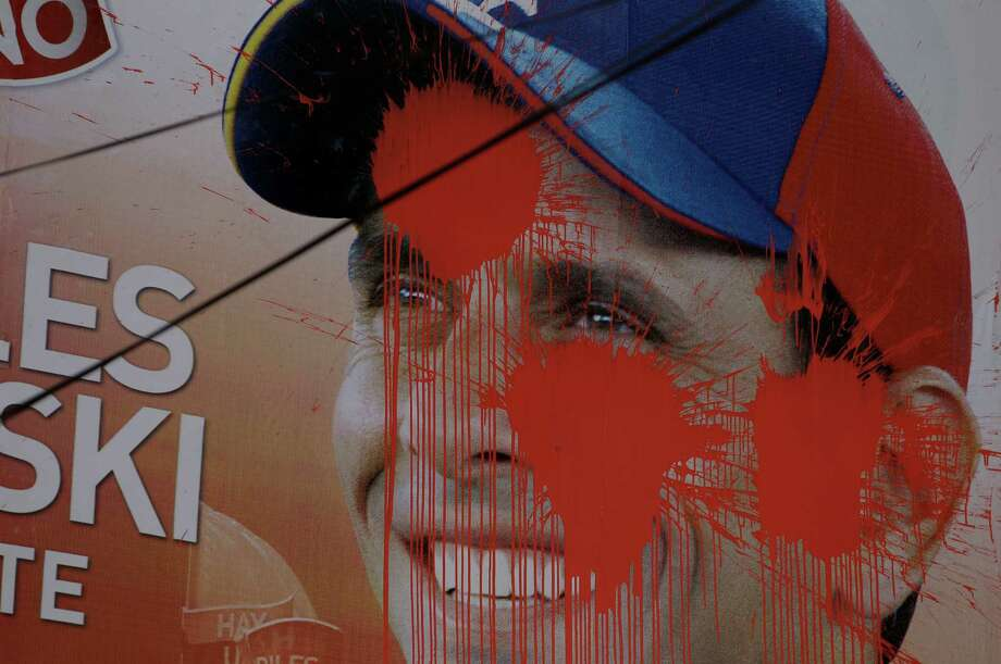 A defaced campaign poster of opposition presidential candidate Henrique Capriles hangs in Caracas, Venezuela, Saturday, Oct. 6, 2012. Capriles is running against President Hugo Chavez in Sunday's presidential election. Photo: Fernando Llano, AP / AP