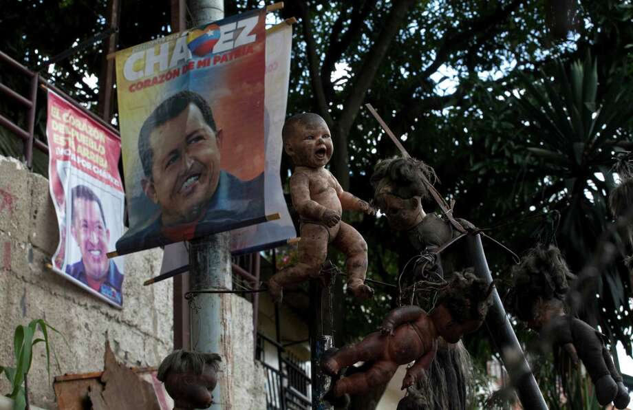 Election campaign posters of President Hugo Chavez hang by dolls on display outside the doll collector's home in downtown Caracas, Venezuela, Saturday, Oct. 6, 2012. Chavez is running for re-election against opposition leader Henrique Capriles in Sunday's presidential election. Photo: Ramon Espinosa, AP / AP