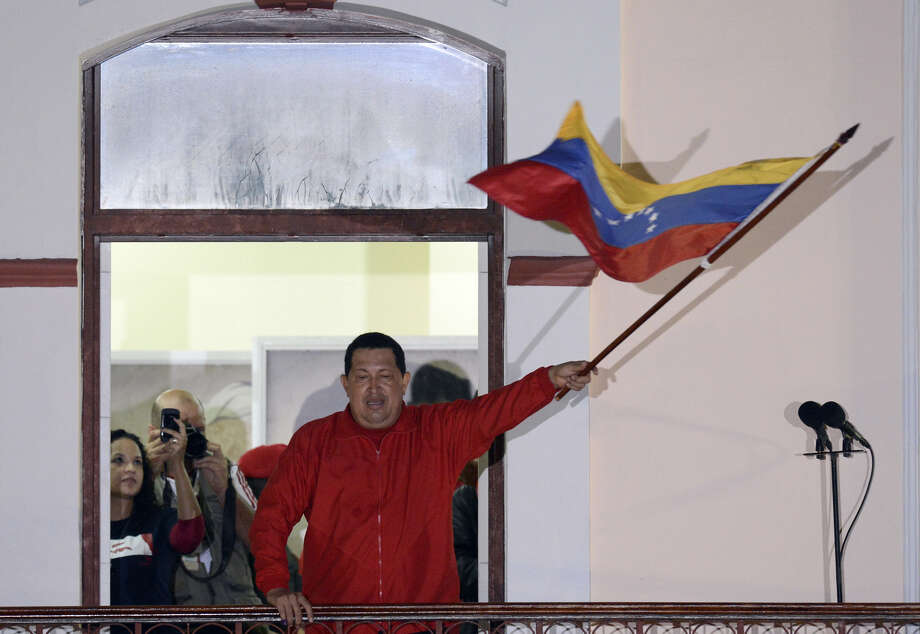 TOPSHOTS  Venezuelan President Hugo Chavez waves a Venezuelan flag while speaking to supporters after receiving news of his reelection in Caracas on October 7, 2012. According to the National Electoral Council, Chavez was reelected with 54.42% of the votes, beating opposition candidate Henrique Capriles, who obtained 44.97%. AFP PHOTO/JUAN BARRETOJUAN BARRETO/AFP/GettyImages Photo: JUAN BARRETO, AFP/Getty Images / JUANBARRETO