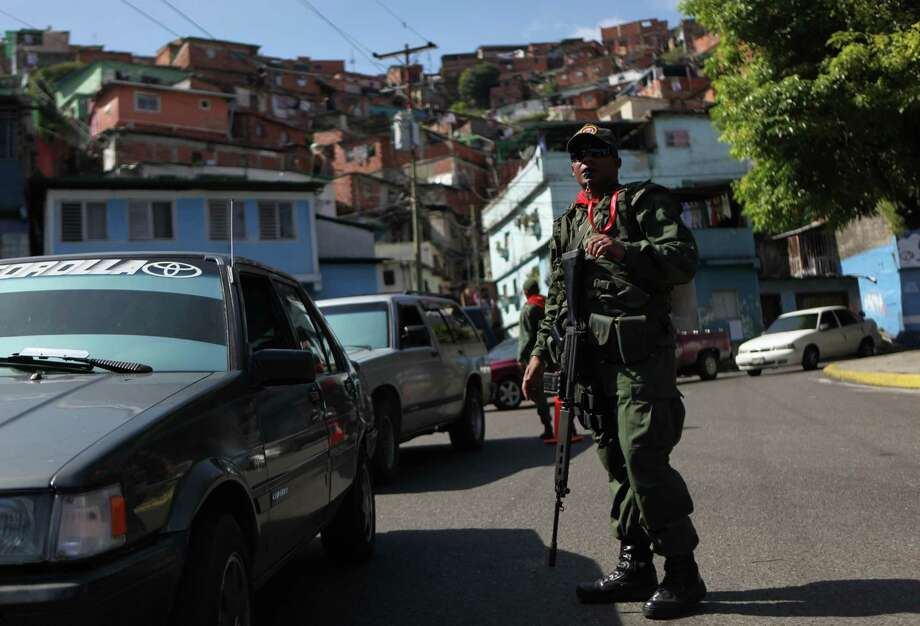 A member of the Bolivarian militia, a militia created by President Hugo Chavez estimated to number more than 100,000 who do not report to the armed forces, stands at a checkpoint in the 23 de Enero neighborhood of Caracas, Venezuela, Saturday, Oct. 6, 2012.  Chavez is running for re-election against opposition candidate Henrique Capriles in Sunday's presidential election. Photo: Rodrigo Abd, AP / AP