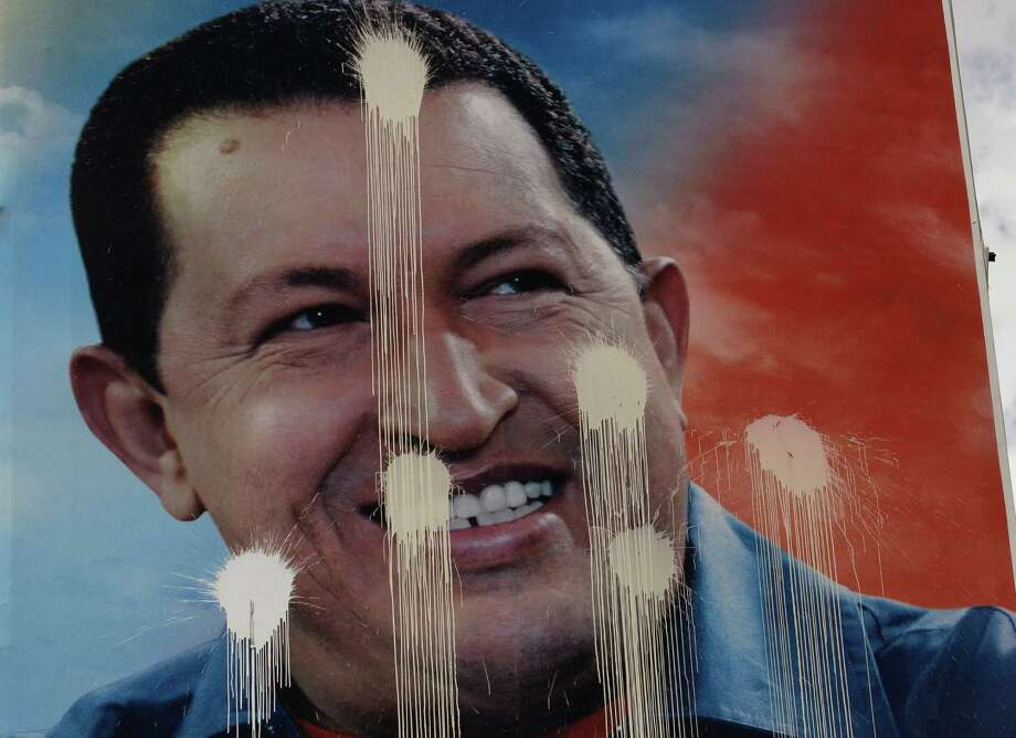A defaced election campaign poster of Venezuela's President Hugo Chavez hangs in Caracas, Venezuela, Saturday, Oct. 6, 2012. Venezuelans will head to the polls Sunday to vote in their country's presidential election, deciding on whether to keep Chavez or seek change. Photo: Fernando Llano, AP / AP