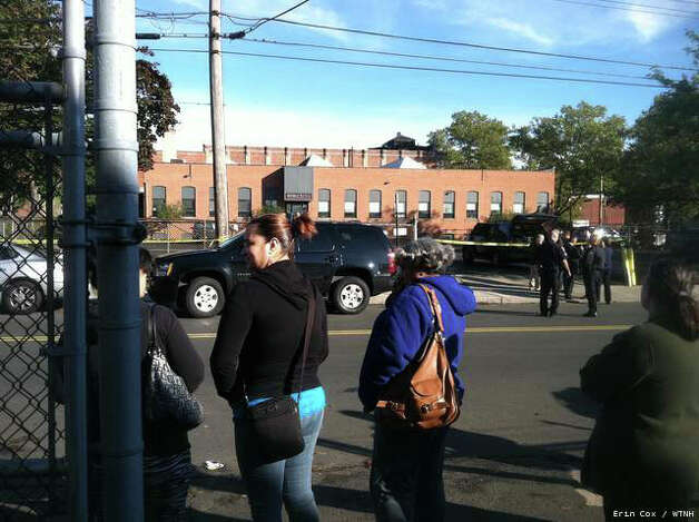 Stunned workers stand outside Electrix in New Haven, where the owner was shot and killed, Oct. 8, 2012. Photo: WTNH News 8