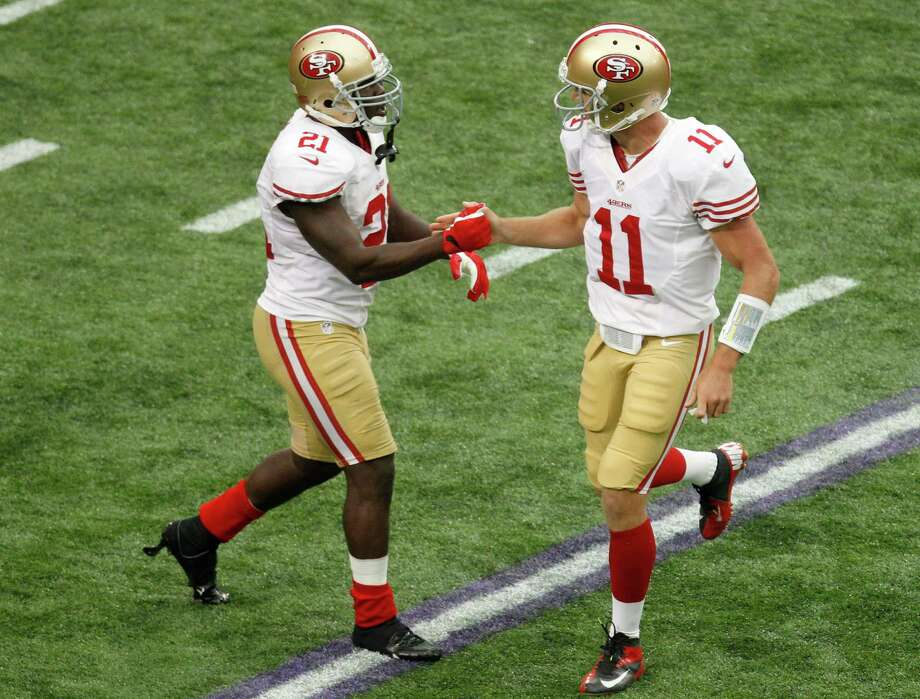 San Francisco 49ers running back Frank Gore, left, celebrates with teammate quarterback Alex Smith, right, after their team scored a touchdown during the second half of an NFL football game against the Minnesota Vikings Sunday, Sept. 23, 2012, in Minneapolis. Photo: Genevieve Ross, Associated Press / FR170496 AP