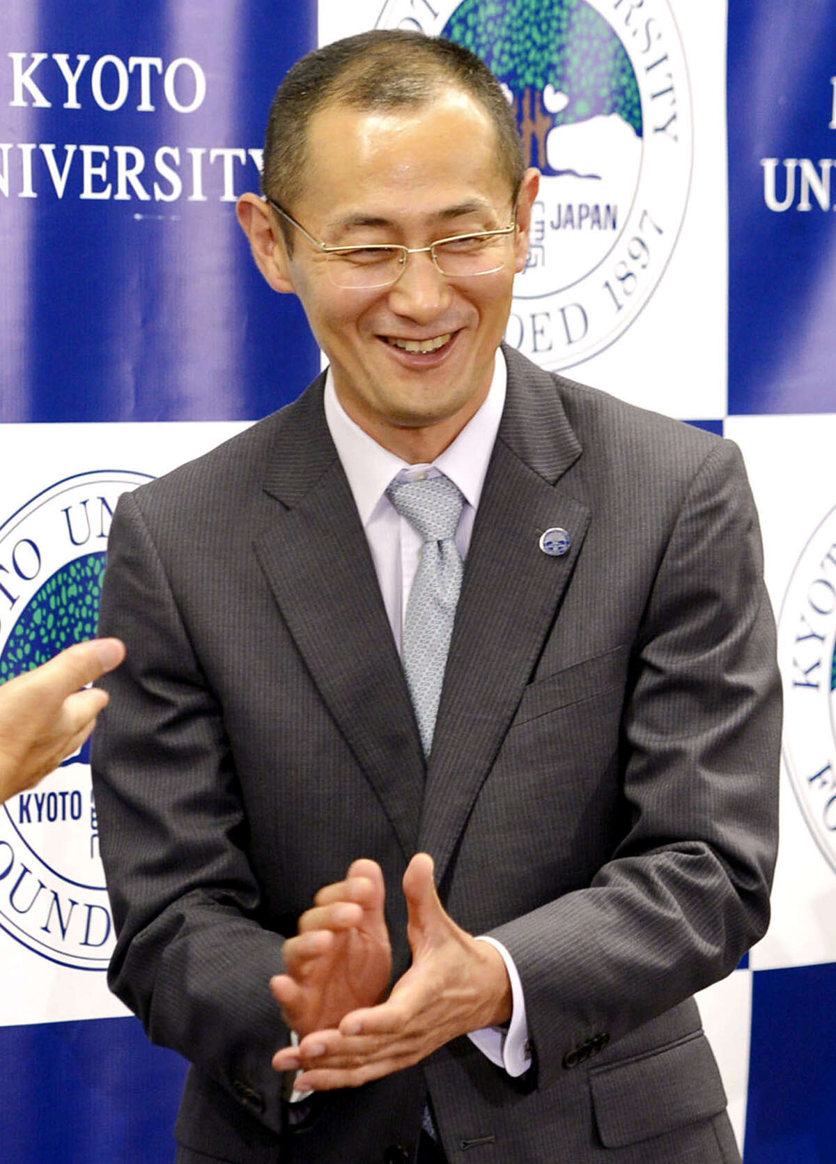 Kyoto University Professor Shinya Yamanaka reacts as journalists applaud the Nobel Prize winner at the end of his news conference at the university in Kyoto, Japan, Monday night, Oct. 8, 2012. Yamanaka and British researcher John Gurdon won this year's Nobel Prize in physiology or medicine. (AP Photo/Kyodo News) JAPAN OUT, MANDATORY CREDIT, NO LICENSING IN CHINA, FRANCE, HONG KONG, JAPAN AND SOUTH KOREA