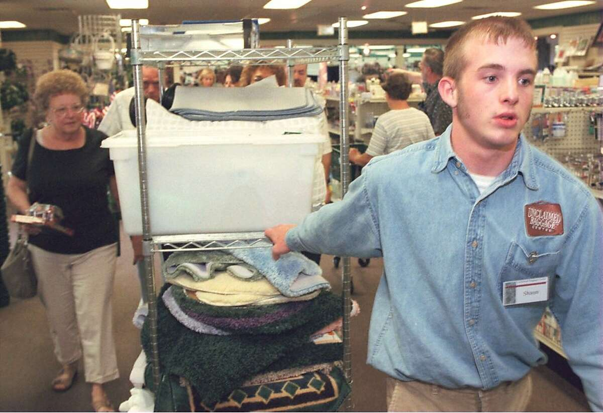 ADVANCE FOR USE ANYTIME-- Shaun Holcomb, 20, pulls a cart with new merchandise through the Unclaimed Baggage Center in Scottsboro, Ala., Sept 8, 2000. Shaun said that the most difficult part of his job is transporting the sale goods through the store with out getting stopped by eager shoppers. The Unclaimed Baggage Center, which opened in 1970 and stretches an entire city block, has an agreement with most U.S airlines to resell unclaimed luggage and its contents for half the original value. The country's largest lost-baggage retailer sells everything from pearls and diamond-studded cuff links to boxer shorts and half-used cans of shaving cream.