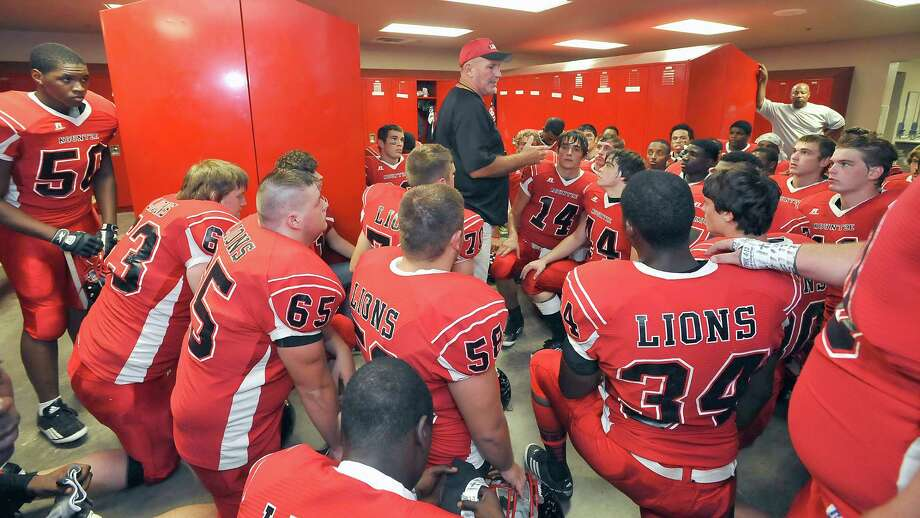 Head Coach Tracy Franklin, center, talks to his team in the locker room before they go out on the field to play Woodville. This was the first home football game in Kountze since the sign controversy started and since the Thursday hearing that determined the cheerleaders could or could not use their faith-based signs.  Kountze hasn't made the playoffs since 1973, but the team is currently 4-1after losing to Woodville Friday night October 5, 2012.  Dave Ryan/The Enterprise