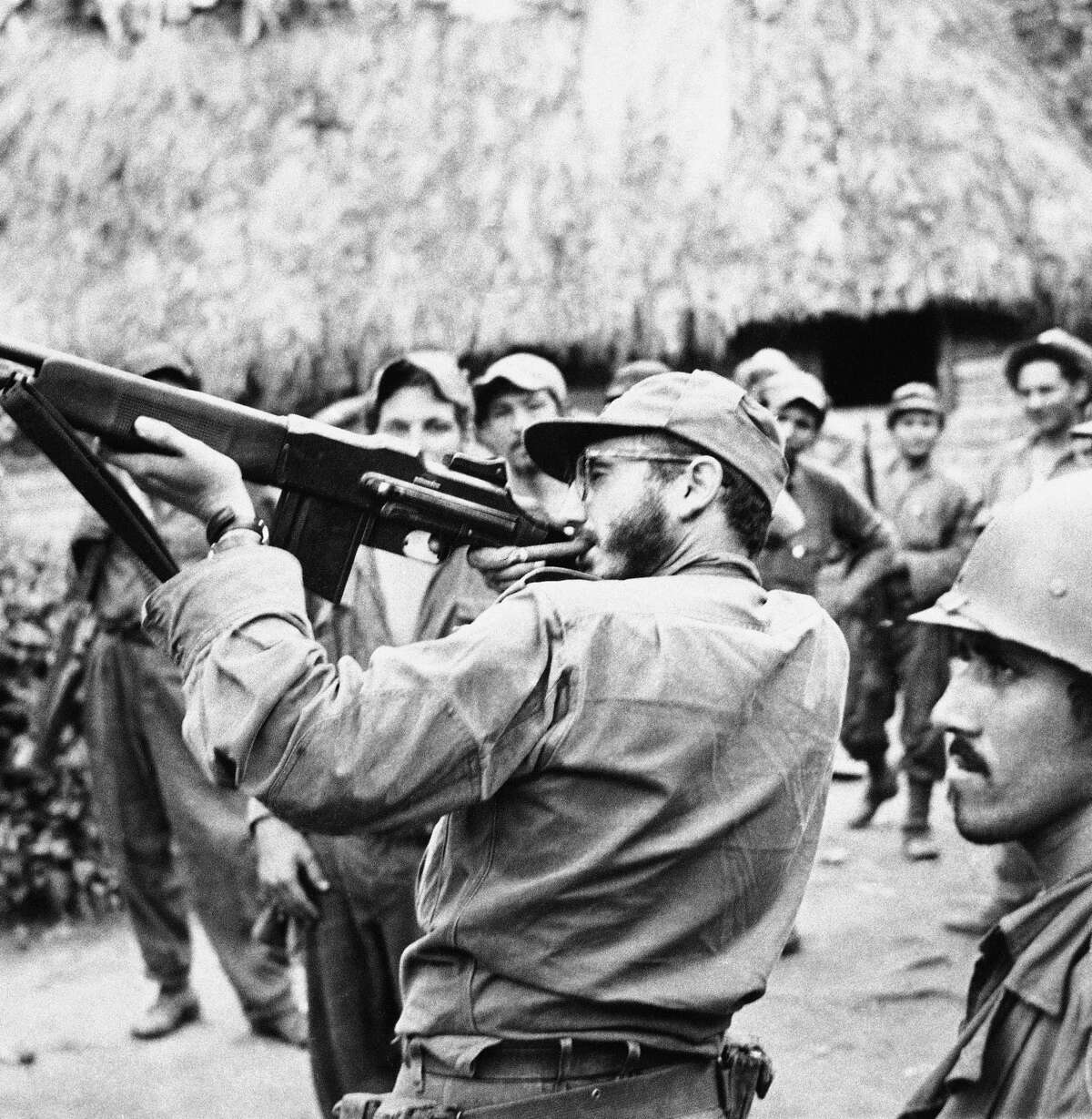 Photos: Fidel Castro, through the years Cuban rebel leader Fidel Castro is shown pointing his rifle during target practice in his Sierra Cristal Mountain hideout, spring 1958. (AP Photo/Andrew St. George)